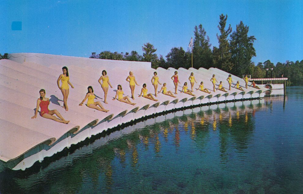 weeki wachee mermaids pose on the roof of the mermaid theater